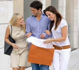 Two happy women and man in the city with shopping bag